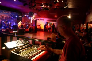 Man stood at a mixing desk in the background an artist is performing