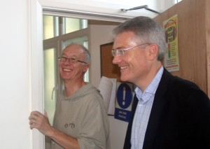 Two men smiling, they are stood in a doorway