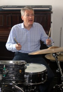 A man sat playing the drums